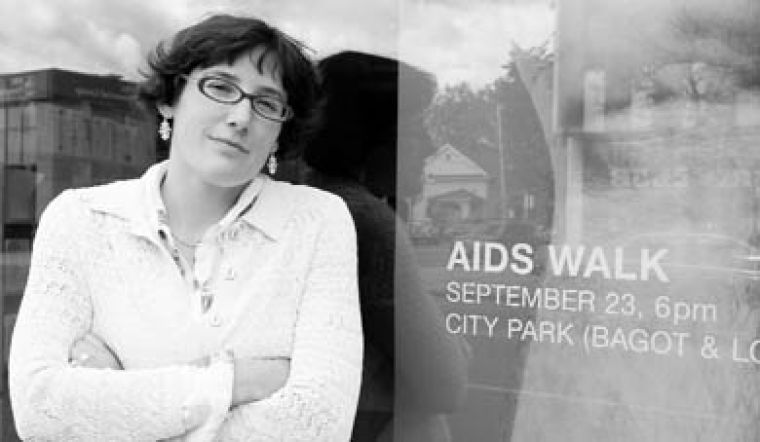 "Marney McDiarmid, an educational co-ordinator at HIV/AIDS Regional Services, stands outside their 844-A Princess Street location in front of posters with slogans such as ""50 per cent of Grade Nine students think there is a cure for AIDS."""