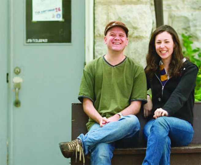 CFRC music co-ordinator Scott Stevens and business manager Joanne Williams sit in front of the entrance to the station's headquarters, located in the basement of Carruthers Hall.