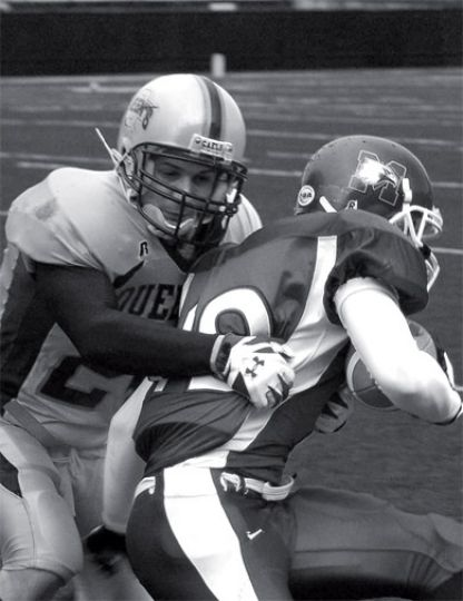 A Queen's defender makes a tackle in last weekend's game.