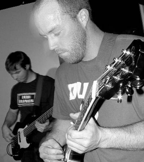 Two members of Grand Theft Bus deliver a few riffs at Elixir.