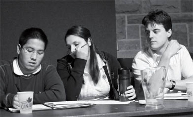 Alvin Tedjo, John Paterson and Liz Craig confer at a debate in the JDUC Wednesday night.