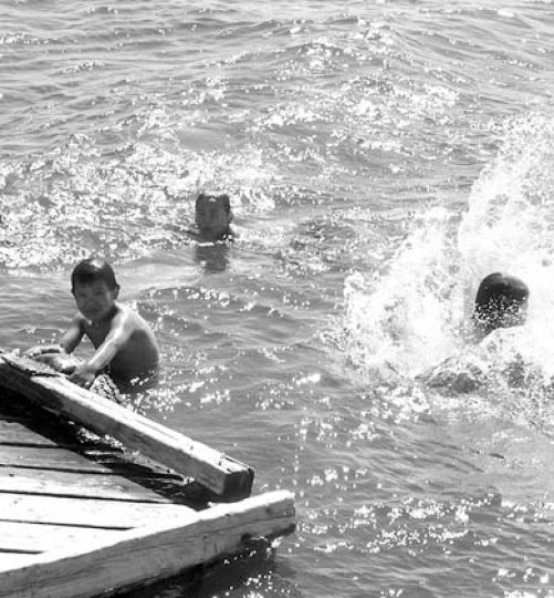 Children from Kitchenuhmaykoosib Inninuwug (K.I.) swim in Big Trout Lake, 600 kilometres north of Thunder Bay.