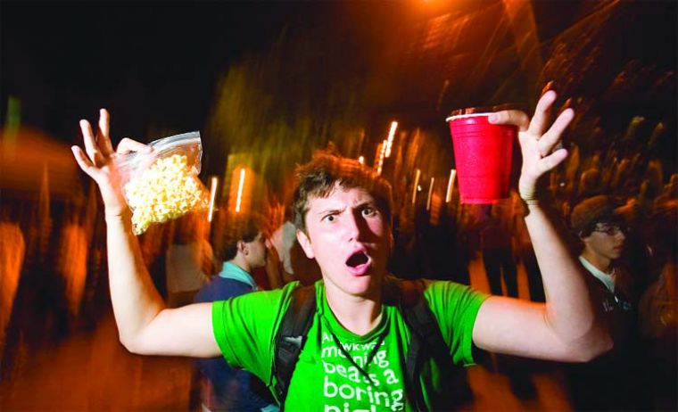 A partier shows off his free popcorn and plastic cup on Aberdeen Street Saturday night. Police said about 8,000 people filled the street.