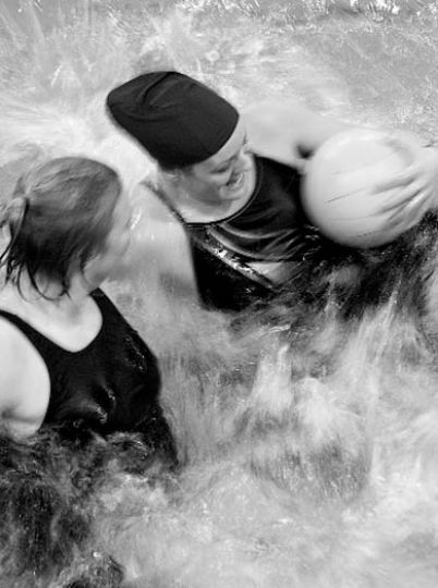 Innertube waterpolo competitors thrash towards the goal.