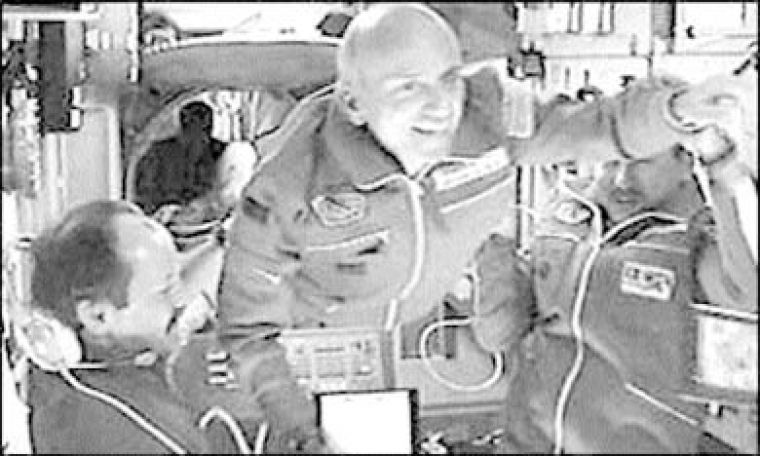 Tito smiles as his crewmates help him aboard the space station.