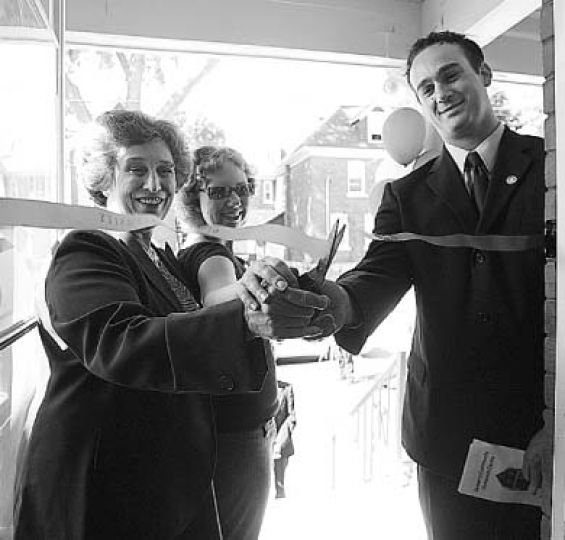 Principal Karen Hitchcock, Deputy Mayor Mark Gerretsen and Megan Krause, ArtSci '08, cut the ribbon at the new community outreach centre.