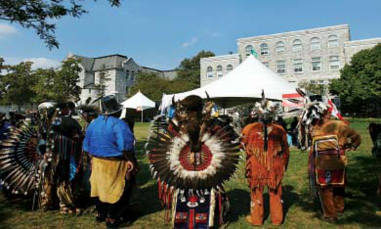 Participants in Queens' first annual educational powwow look out across Agnes Benidickson field Saturday morning.