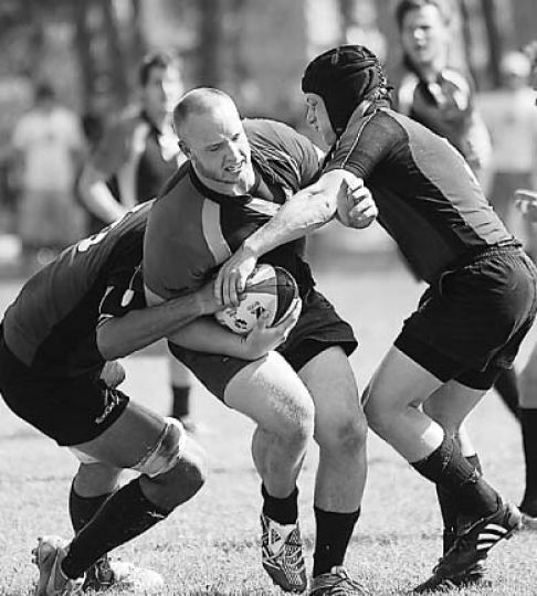 Several McMaster tacklers try to bring down Steve Shortly in Saturday's rugby match.