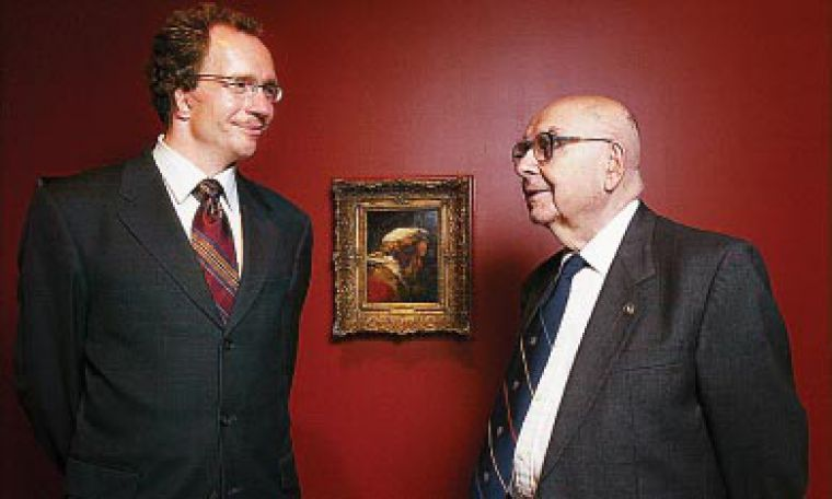Alfred Bader, right, stands with Agnes Etherington Art Centre curator David DeWitt and Rembrandt's Head of a Man in a Turban, in Profile. The painting is the second Rembrandt the Baders have donated to Queen's.