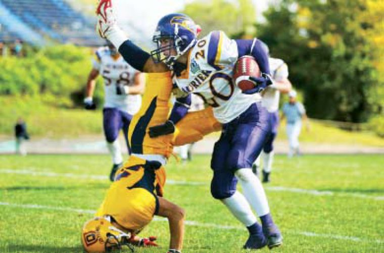 Queen's defensive back Addison Rich does a faceplant in Saturday's loss.