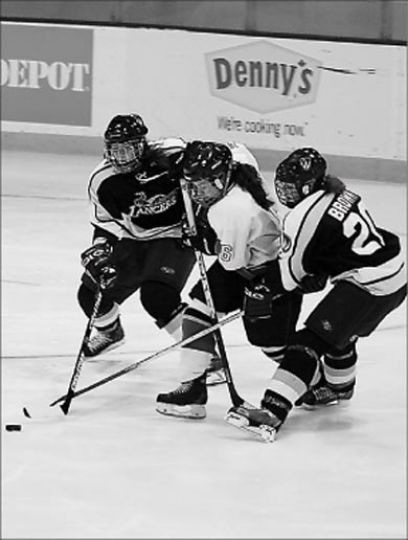 Becky Conroy battles two Lancers for the puck Saturday.