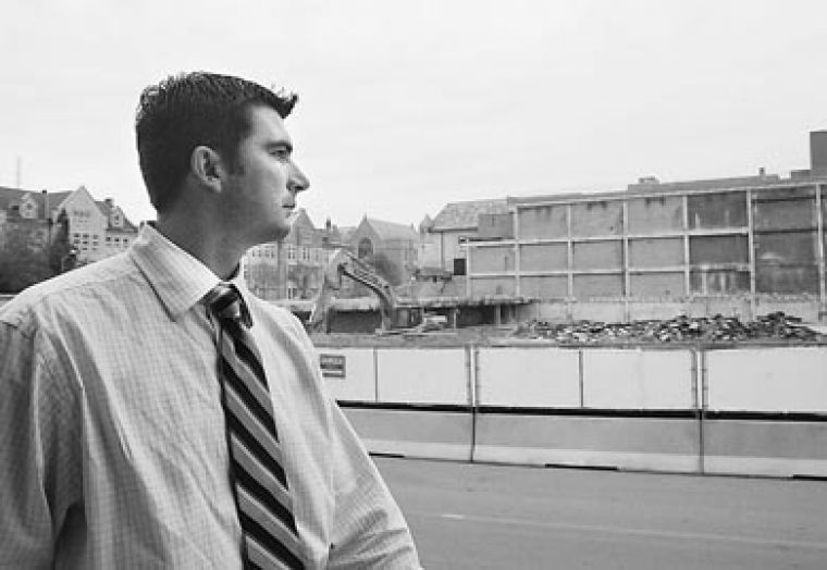 Men's hockey coach Brett Gibson outside the ruins of Jock Harty Arena. The arena's loss may lead to ice hockey being cut.