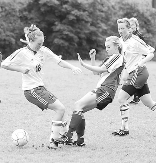 Defender Ali Skinner (18) battles for the ball as teammate Erin Smith looks on.