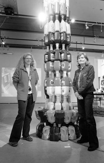"Lisa Figge poses with Anna Elmberg Wright beside her laundry detergent sculpture, titled ""Tower."""