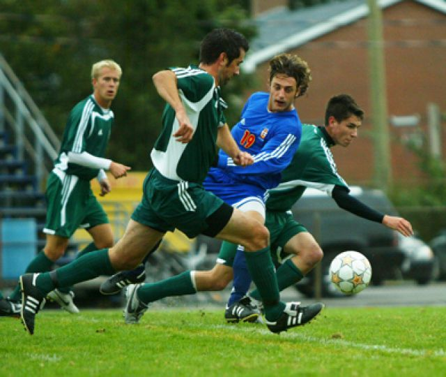 Nick Milonas (19) battles two members of the Trent Excalibur for the ball Sunday. Queen's and Trent played to a 0-0 draw.