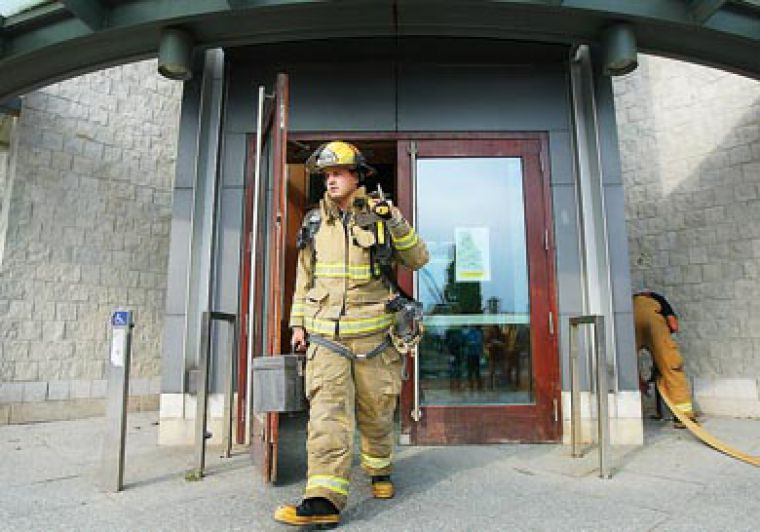 Kingston firefighter Shawn Wellbanks exits Stauffer Library following a fire scare on Wednesday.