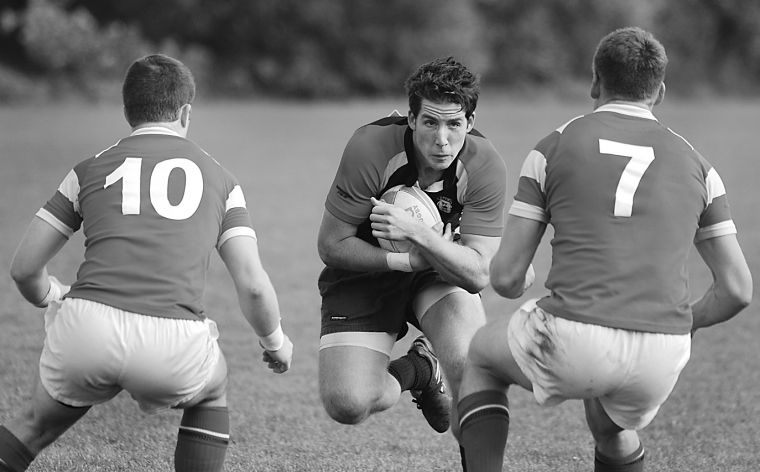 Gaels' rugby captain James Potter takes on two Royal Military College defenders Saturday. The Gaels beat the Paladins 41-0.