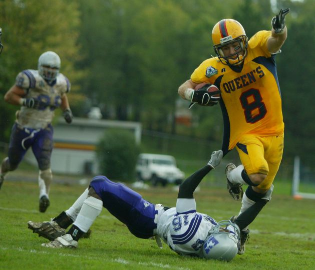 Gaels' slotback Rob Bagg, in his last CIS football game, is tackled by Western's Kelvin Mwangi.