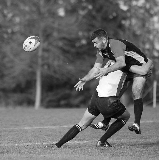 Gaels' flyhalf Mike Simmons gets hit by OUA final MVP Ray Barkville of Brock Saturday.