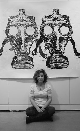 "Artist Jacqueline Collomb poses in front of a woodcut titled ""Gas Mask."""