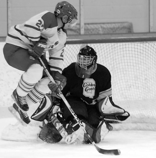 Queen's goalie Ryan Gibb makes a save on RMC forward Josh Fudge on Wednesday. Gibb made 31 saves en route to a 3-2 win.