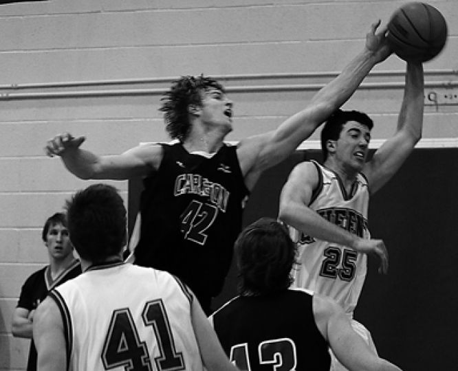 Queen's forward Nick DiDonato (25) is blocked by Carleton star Aaron Doornekamp Friday.