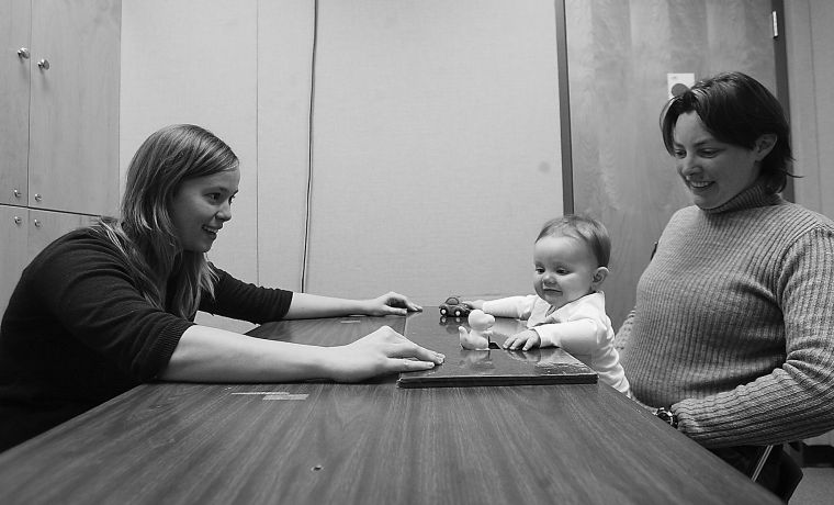 Brynn Evans, eight-month-old subject at the Infant Cognition Lab, is given two toys to choose from graduate student Liz Hallinan as Brynn's mother, Christa Moran, looks on.