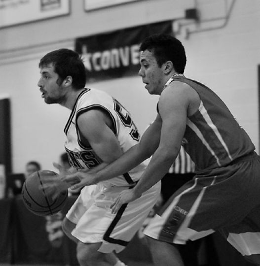 Queen's point guard Baris Ondul drives against RMC's Gavin Viray-Cox Wednesday night.