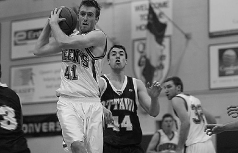Queen's guard Simon Mitchell grabs the ball Jan. 29 against the University of Ottawa. Mitchell was named an OUA East Second Team All-Star March 6 after averaging 12.2 points per game.
