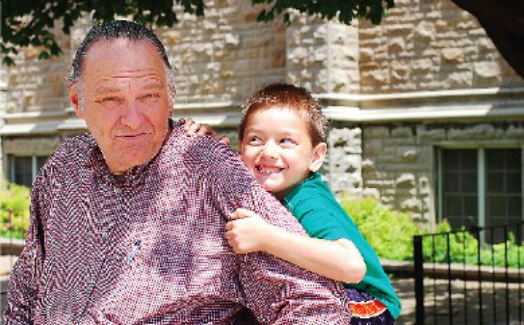 Robert Lovelace, shown with his son River, 6, says he will return to his teaching position at Queen's in September.