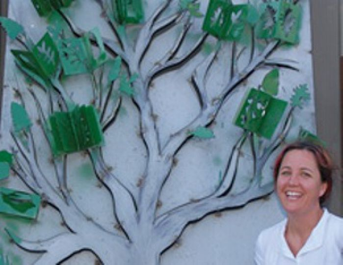 Local artist Rebecca Soudant, who works in a variety of media and often collaborates, poses with her latest piece, a metal sculpture titled A Knowledge Tree: Nature's Own Story.