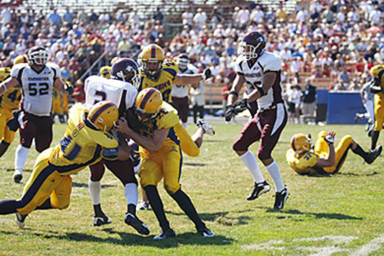 Queen's linebacker T.J. Leeper (41) and defensive back Alex Daprato bring down McMaster running back Tony Okorodudu Monday. The Gaels beat the Marauders 35-11.