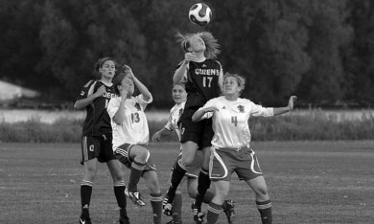Queen's midfielder Erin Smith (17) goes up for the ball against RMC.