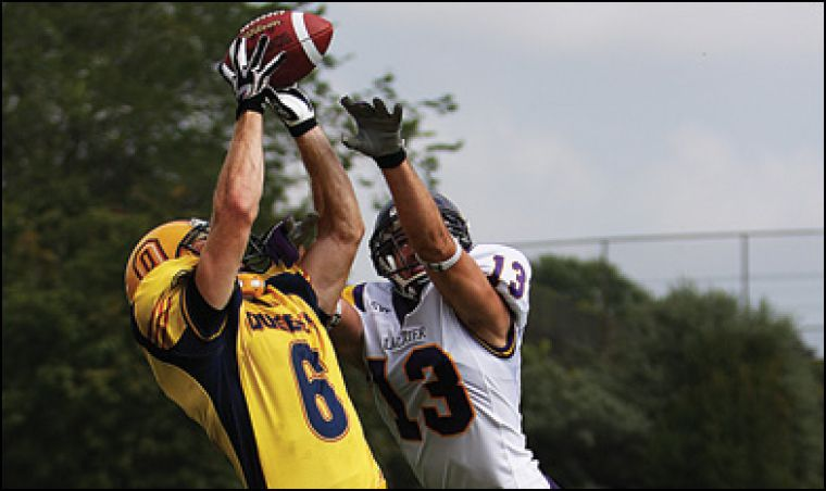 """Queen's wide receiver Blaise Morrison makes a catch Saturday at Richardson Stadium against Laurier's Giancarlo Rapanaro. The Gaels won 41-7. See Sports section, article """"Gaels taste revenge,"""" for full story."""