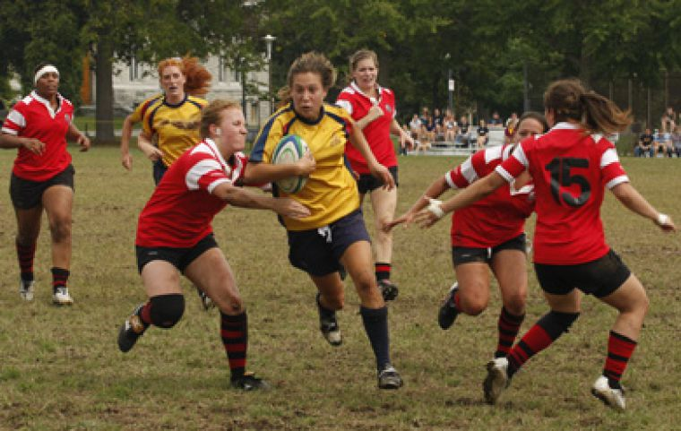 Queen's Julie Englehardt is pulled down by York's Dasha Kornienk Sunday. Queen's won 31-0.