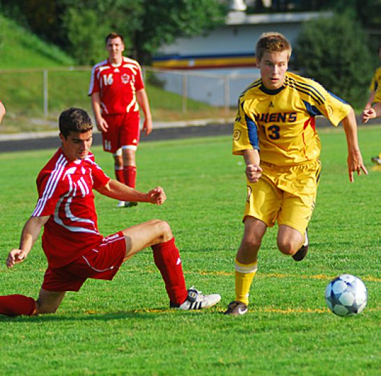 Gaels' midfielder Andrew Colosimo dribbles past RMC's Alexi Ouellet as fellow Gael Steve Irish looks on.