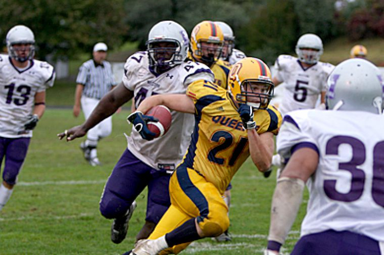 "Gaels' running back Mike Giffin tries to evade three Western defenders Saturday in Queen's 43-16 Homecoming win. Please see article ""New gridiron stars shining for Gaels"" in the Sports section for a column on the game."