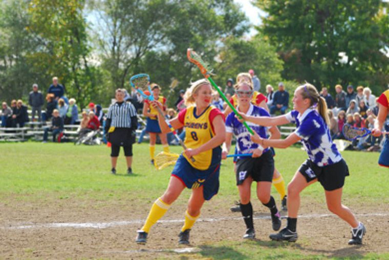 Queen's Carley Miller avoids a stick lift from Western's Adrianna Clapp Saturday.