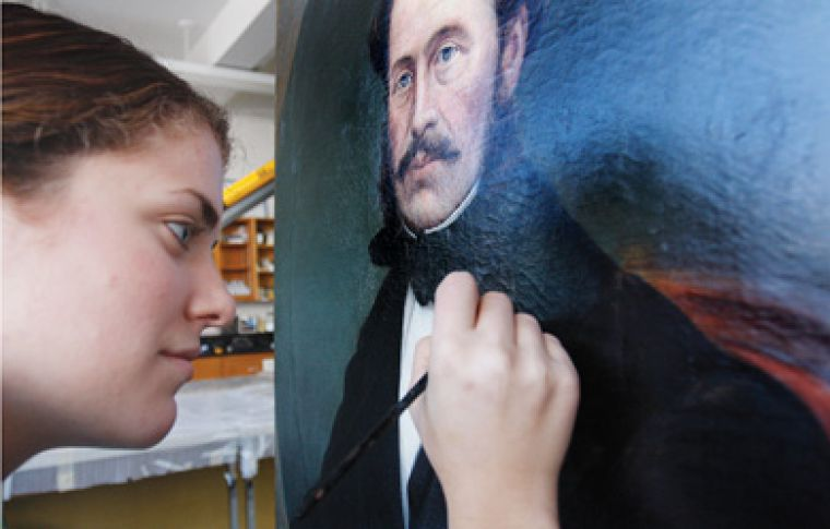 Christina St. Germain, MA '09, restores a painting at the Agnes Etherington Art Centre. For full story, see the Features section.