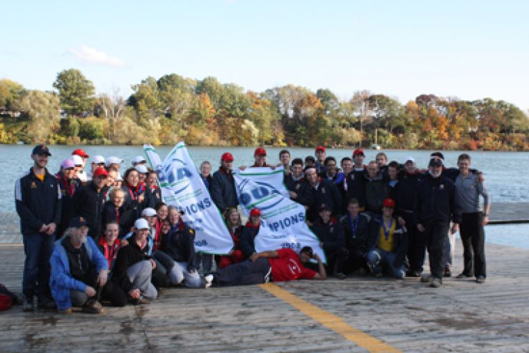 The men's and women's rowing teams pose with their OUA championship banners on the dock in St. Catharines Saturday.