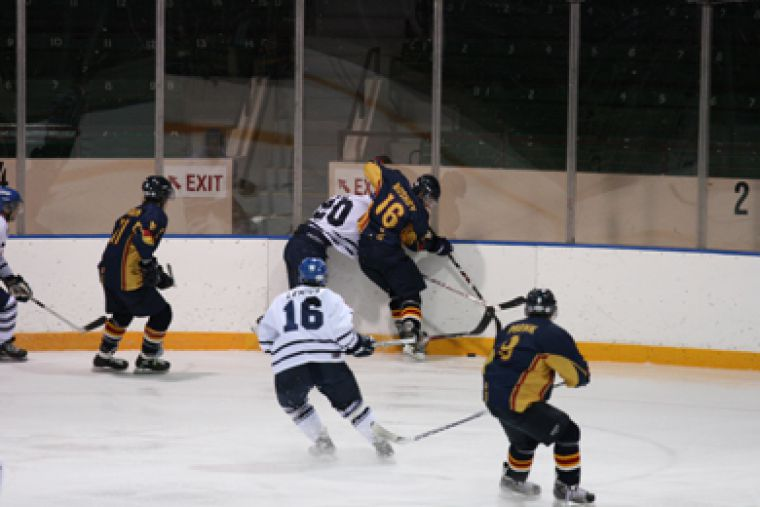 Queen's defenceman Mike Bushby drives University of Toronto Varsity Blues' forward Robert Kay into the boards Saturday night at the Memorial Centre. The Gaels won 4-1.