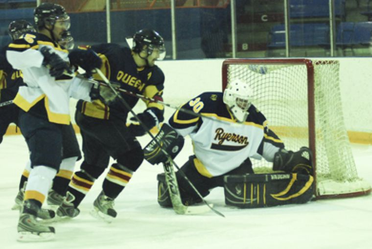 Queen's forward Billy Burke drives to the net against Ryerson Friday.