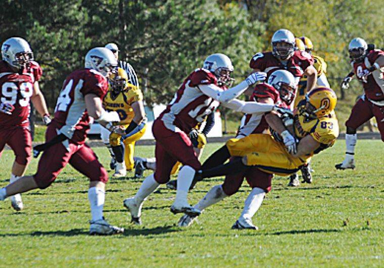 Queen's receiver Scott Stinson is tackled by a group of Gee-Gees Saturday. The Gaels were knocked out of the playoff in the semifinal game, losing 23-13 to Ottawa. Please see page 16 for full story. Visit queensjournal.ca for a photo gallery of the game.