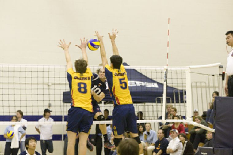 Queen's Sam Pedlow (8) and Joren Zeeman go up for a block against Toronto's Jessi Lelliot Friday.