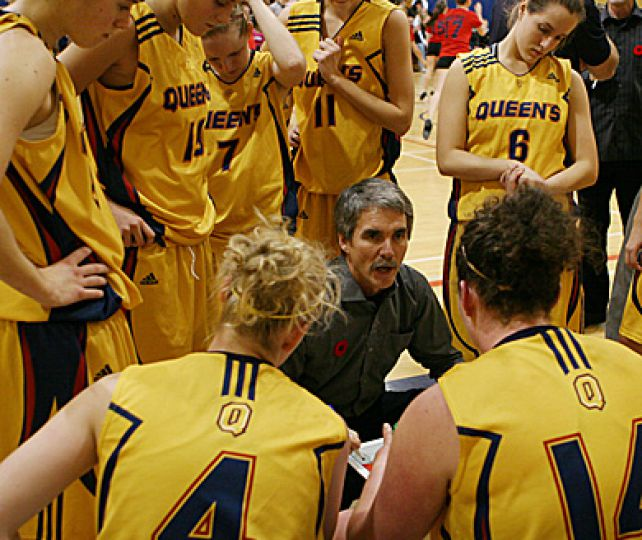 Head coach Dave Wilson talks to his team during a break in play Saturday night. The Gaels won 89-69.