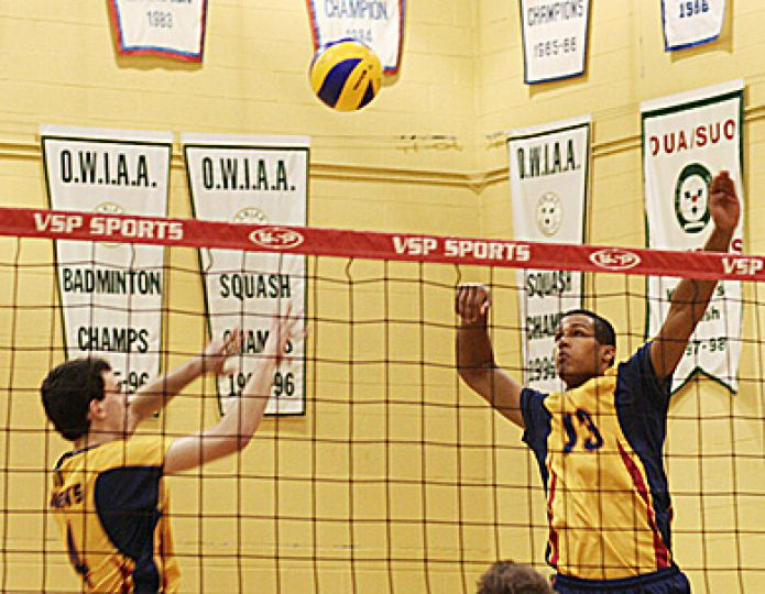 Men's volleyball setter Dan Rosenbaum (4) sets middle hitter Michael Amoroso up for a spike Saturday night against the Laurier Golden Hawks at Bartlett Gym.