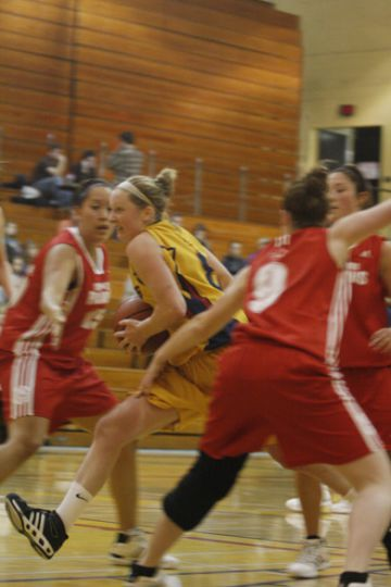 Queen's guard Brittany Moore drives against RMC's Samantha Bayne (9) and Anna Dupuis (15) Wednesday. Moore scored a school-record 40 points in the Gaels' 79-64 victory.