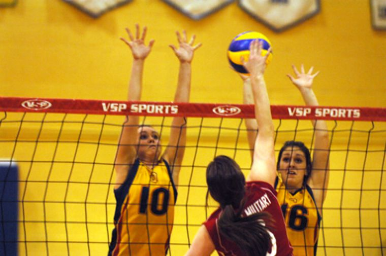 RMC's Rebecca Fielding goes for a kill Wednesday against Queen's Becky Billings (10) and Leah Franco (16). The Gaels beat the Paladins in straight sets.