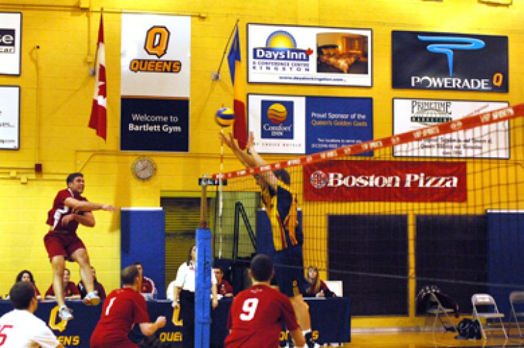 RMC middle hitter Paul Demers tries to get a hit past Queen's blockers Matthew Taylor (left) and Darren Edwards.