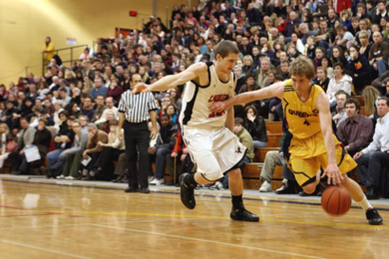 Gaels guard Dan Bannister attempts to outmaneuver captain Stuart Turnbull of the Carleton Ravens. For full story, refer to the sports section.
